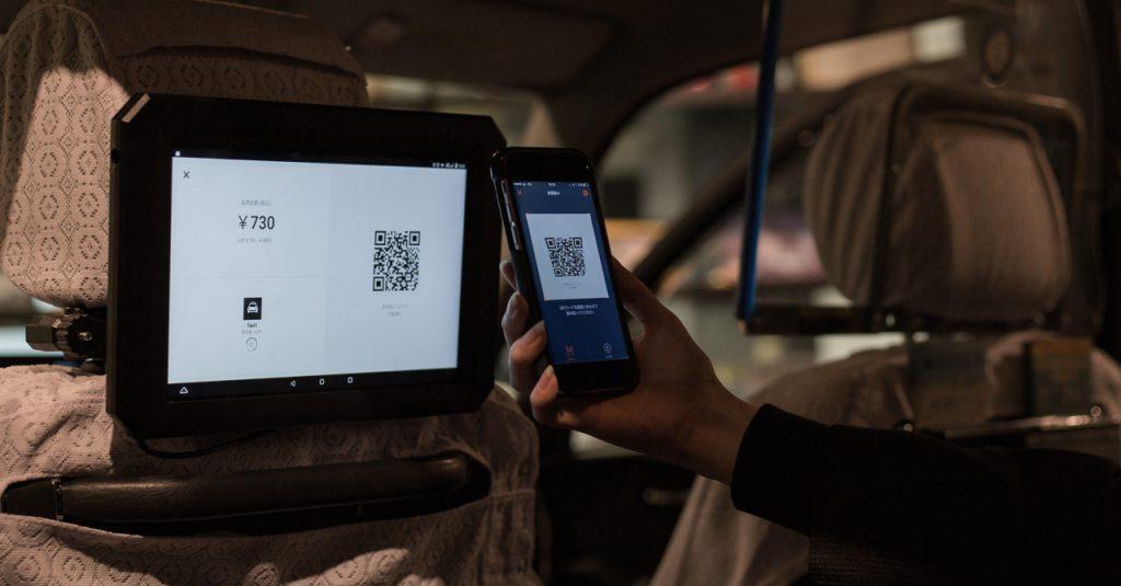日本交通タクシー車内でのOrigami Pay支払方法。サイネージ端末に表示されたQRコードをスマートフォンで読み取る(出典:Origamiの広報発表文より)