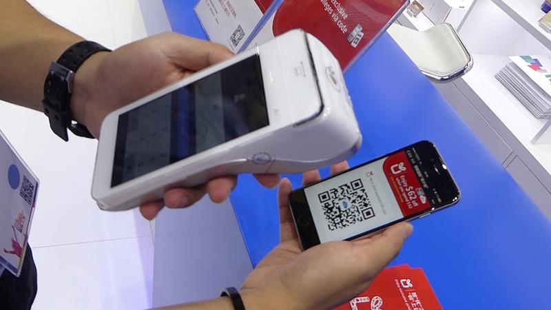 ▲利用者のスマートフォンに表示されたU PlanのQRコードクーポンを、お店の読み取り端末でスキャンし、割引された金額でカード決済するデモ